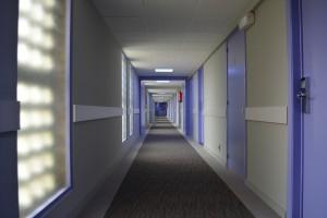 Dark gloomy, sparse hotel hallway with purple room doors.