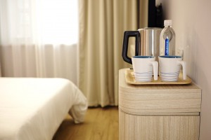 Hotel room with ameneties that include little more than water and coffee maker
